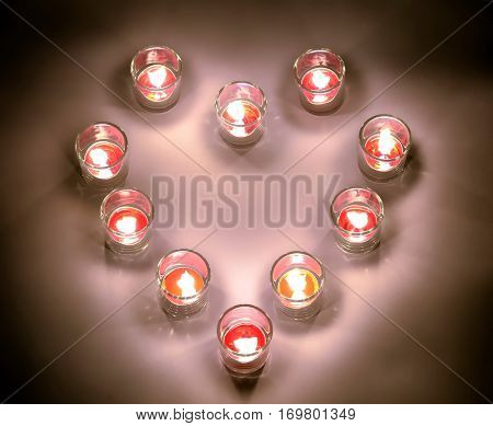 A small lighting lamps with red color aromatic paraffin in a small glasses arrange in heart form on a white floor in the night