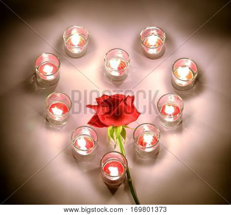 A small lighting lamps with red color aromatic paraffin in a small glasses arrange in heart form around the red rose symbol of love and valentine's day on a white floor in the night