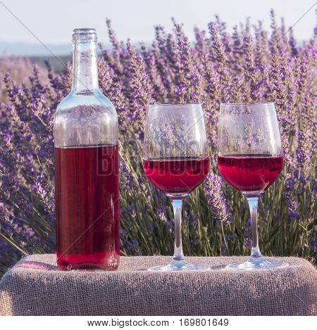 A square photo of rose wine glasses and a bottle in a lavender field. The glasses are on a crate with a burlap texture, with a retro corkscrew and a cork, slightly toned