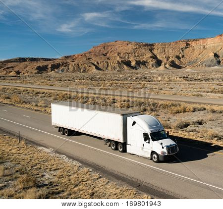 A white big rig rolls across Utah on a devided highway