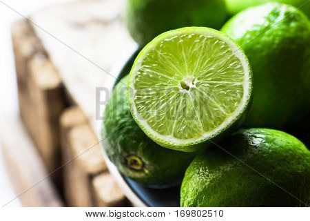 Heap of ripe organic limes cut in half in the sunlight,on vintage wood, ingredients for infused detox drinks, citrus, cleansing, health,diet