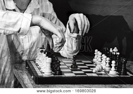 Monochrome photography of chess player. Women's hands are arranging chess pieces on the board