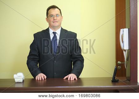 Solid concierge behind the counter at his workplace in a luxury apartment building