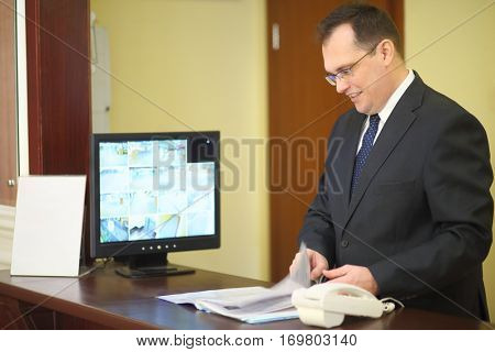Concierge behind the counter at his workplace leafing through a magazine in a luxury apartment building