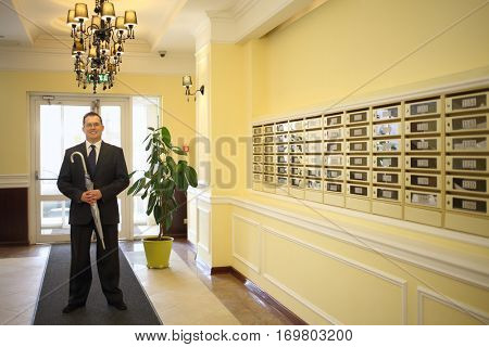 Handsome man in a business suit and tie holds a silver umbrella in the hallway near the mailboxes