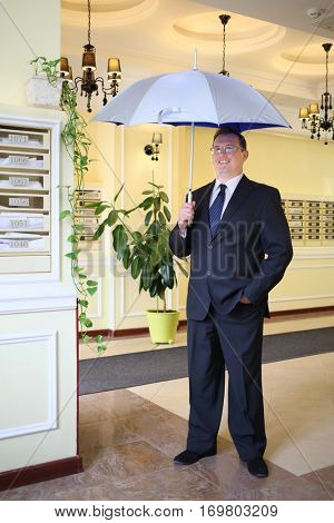 Handsome man in a business suit and tie standing with an open silver umbrella in the hallway near the mailboxes