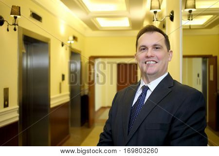 Portrait of smiling concierge in a business suit standing in the hallway between the elevator and mirrors in the luxury apartment building