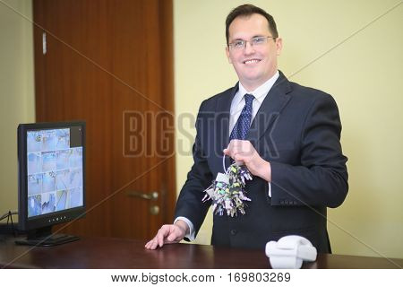 Smiling concierge with a big bunch of keys near the monitor with CCTV