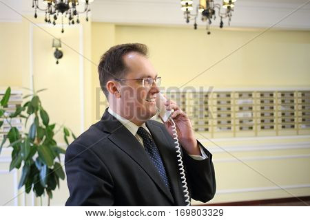 Man in a business suit talking on the phone in the hallway of the luxury apartment building