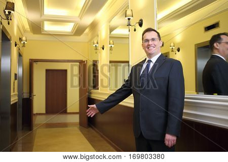 Hospitable concierge in a business suit standing in the hallway between the elevator and mirrors and inviting to enter the house