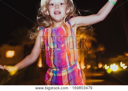 Little girl jumping and having fun. Summer night. Happy child. Motion photo. Natural Beauty.