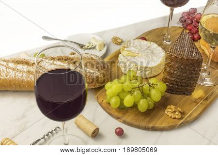 A photo of a wine and cheese tasting, with bread, grapes, and a glass of red wine, with a place for text