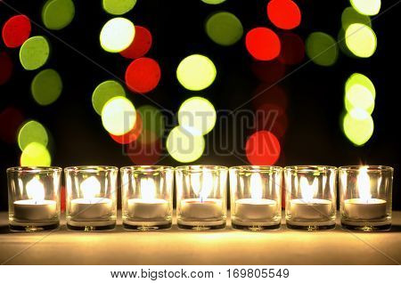 Seven of small glasses that have a small lighting lamps inside arrange in a row with a round yellow and red bokeh of blur light bulb in the back ground