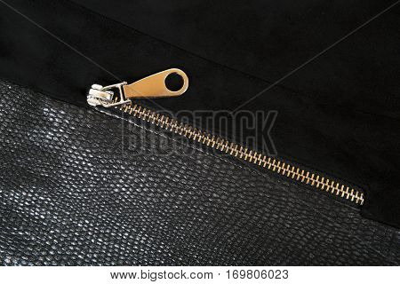 Gold zipper on the background of skin and nubuck