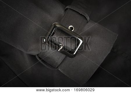 Black plastic buckle of a raincoat on black fabric background