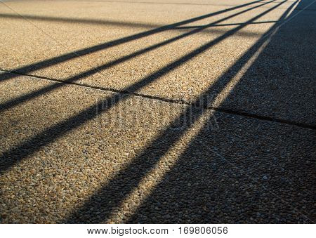 Shadow of steel fence grafted onto rough anti-slip concrete floor