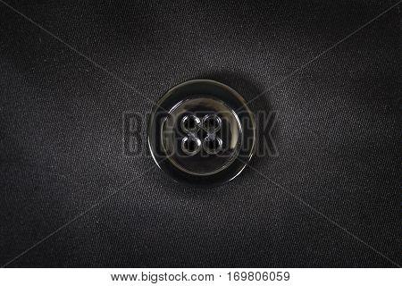 Black plastic button is sewn on black fabric