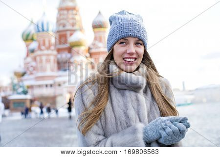 Portrait of a young woman in a blue knitted hat and gray mink coat, posing in winter Red Square in central Moscow