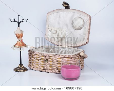 Composition of opened beige-coloured box with stand for bijouterie and pink candle isolated on white background. Handmade decoupage box. Orange mannequin styled stand for bijouterie.
