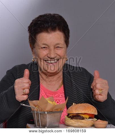 Funny grandmother eating a big burger and fried potatoes.