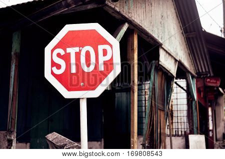 stop sign against the backdrop of dilapidated ramshackle housing