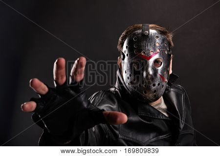 Maniac in hockey mask on dark background
