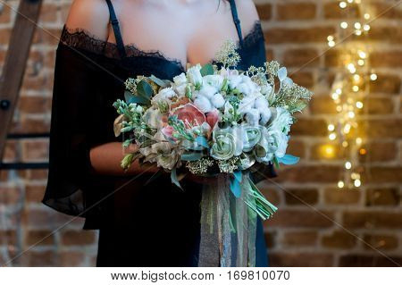 Bridal bouquet with cotton. Wedding. The bride in black dressing gown standing on a loft background with garlands and holds a wedding bouquet with white, pink, gold flowers and greenery, decorated with long silk ribbon