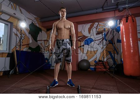 Young man working out with battle ropes at crossfit gym. Exercising at the gym