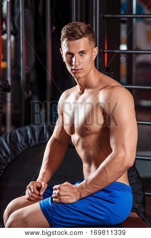 Portrait of handsome sportive man in gym. Beautiful relief male torso