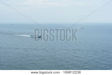 Three different ship floating in the sea at different speeds. Sea in this case, a huge lake Baikal. In the foreground is a small cruise liner ship. Behind are two hydrofoils.