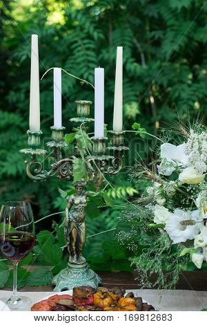 Antique candlestick in the form of female figurines on a table on a green background with candles. Table served with plate of grilled vegetables, glass of red wine and bouquet with white flowers and greenery, summertime.