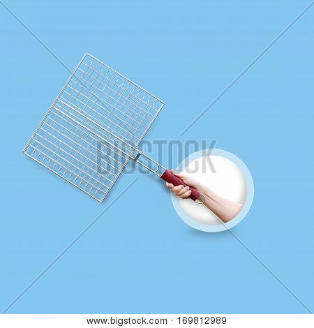 Steel Grid For Grill In Hand Isolated On A Blue Background.