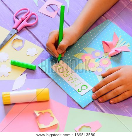 Creating a greeting card with flowers for mom. Child holds a pen in hand and writes 8 March. Tools and materials for children's art activity. March 8 greeting card crafts concept