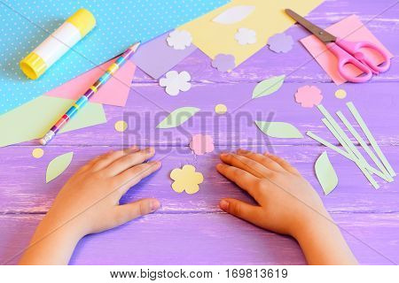 Small child makes a greeting card for mother. Colored paper, templates, flowers and leaves cut from paper, scissors, glue stick, pencil on a wooden table. Children's crafts for mother's day or March 8