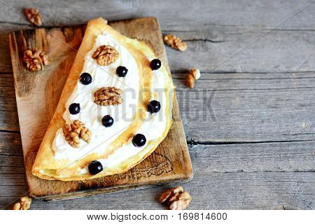 Delicious omelette with soft curd cream, walnuts and black currants on a wooden board and vintage background with copy space for text. Healthy omelette idea