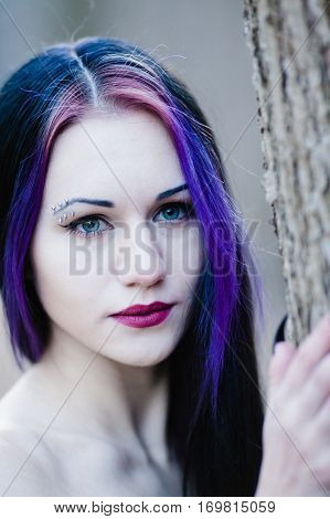 Close-up portrait of woman in the dark winter forest in gothic style