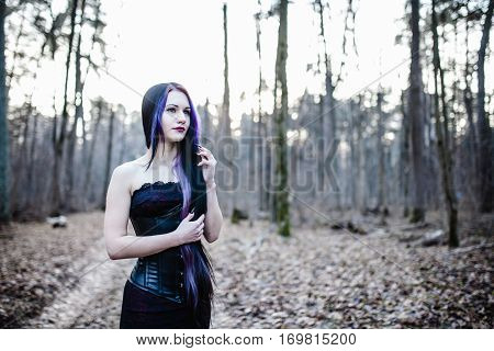 Portrait of the gothic woman in the dark winter forest