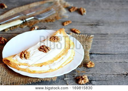 Homemade vegetarian omelette on a white plate. Omelet stuffed with sweet cottage cheese and walnuts. Fork, knife, shelled walnuts on vintage wooden table