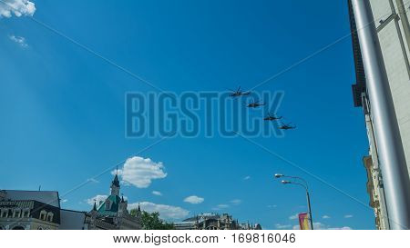 Four combat helicopters flying over the city