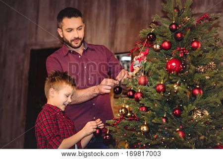 Little son with happy father decorating christmas tree