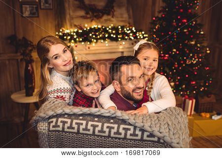 Happy family smiling at camera at christmastime