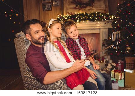 Happy family taking selfie at christmastime near fireplace at home