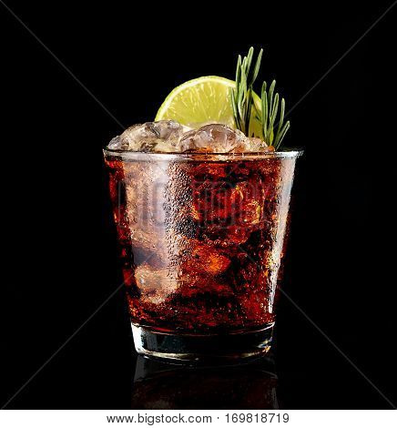 cola drink with ice and green lime on black background