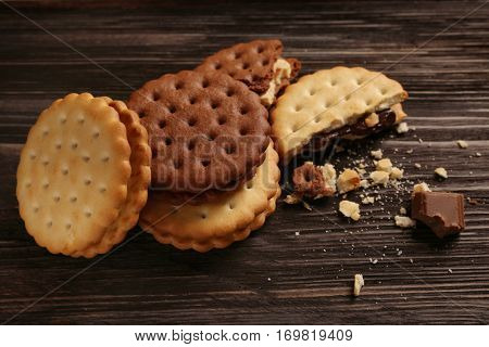 Tasty cookies with crumbs on wooden background