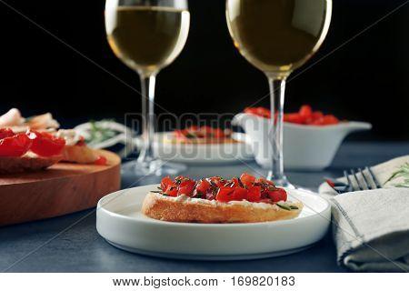 Tasty bruschetta served with wine on table on black background