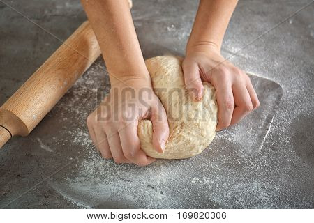 Woman hands kneading dough on kitchen table