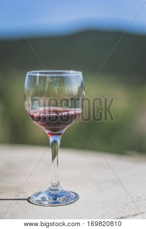 Glass of red wine on table at winery