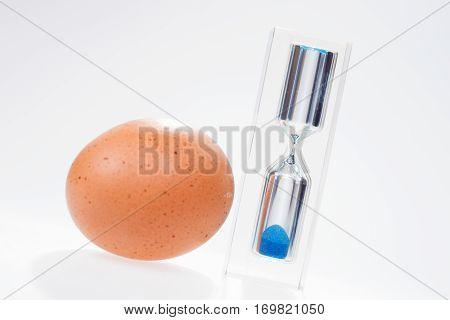 Chicken egg with modern glass egg timer. Sand clock