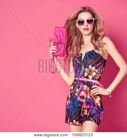 Fashion woman in Trendy Spring Summer Dress. Stylish wavy hairstyle, fashion Sunglasses, Summer Floral Outfit. Glamour Blond lady in Sexy Jumpsuit, fashion pose. Playful Girl, Luxury summer Pink Clutch