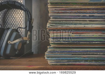 Pile of old vinyl records and headphones near the speaker on the table